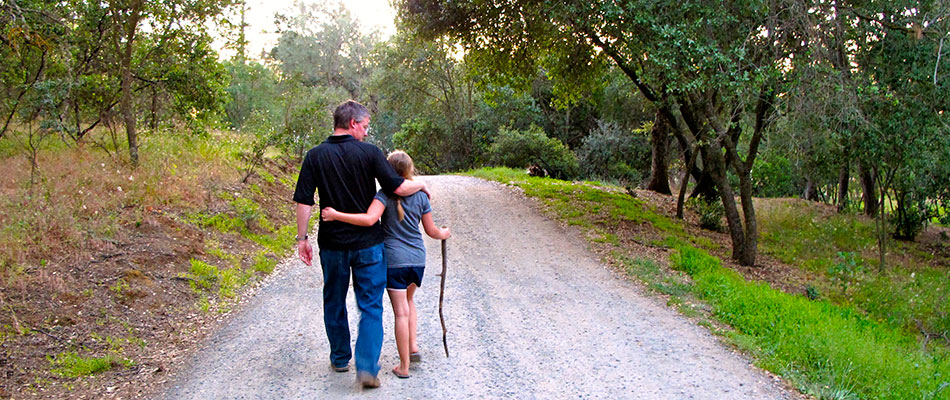 Andrew Tanis walking down a road less traveled with his daughter in Amador Wine Country near Tanis Winery.